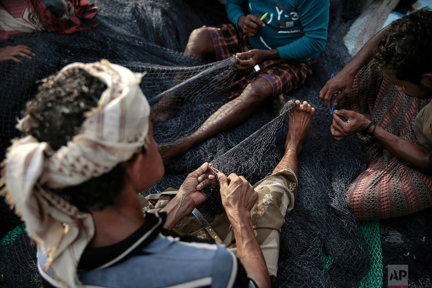 In this Sept. 29, 2018, photo, fishermen fix their nets before a fishing trip at the main fishing port, in Hodeida, Yemen. (AP Photo/Hani Mohammed)