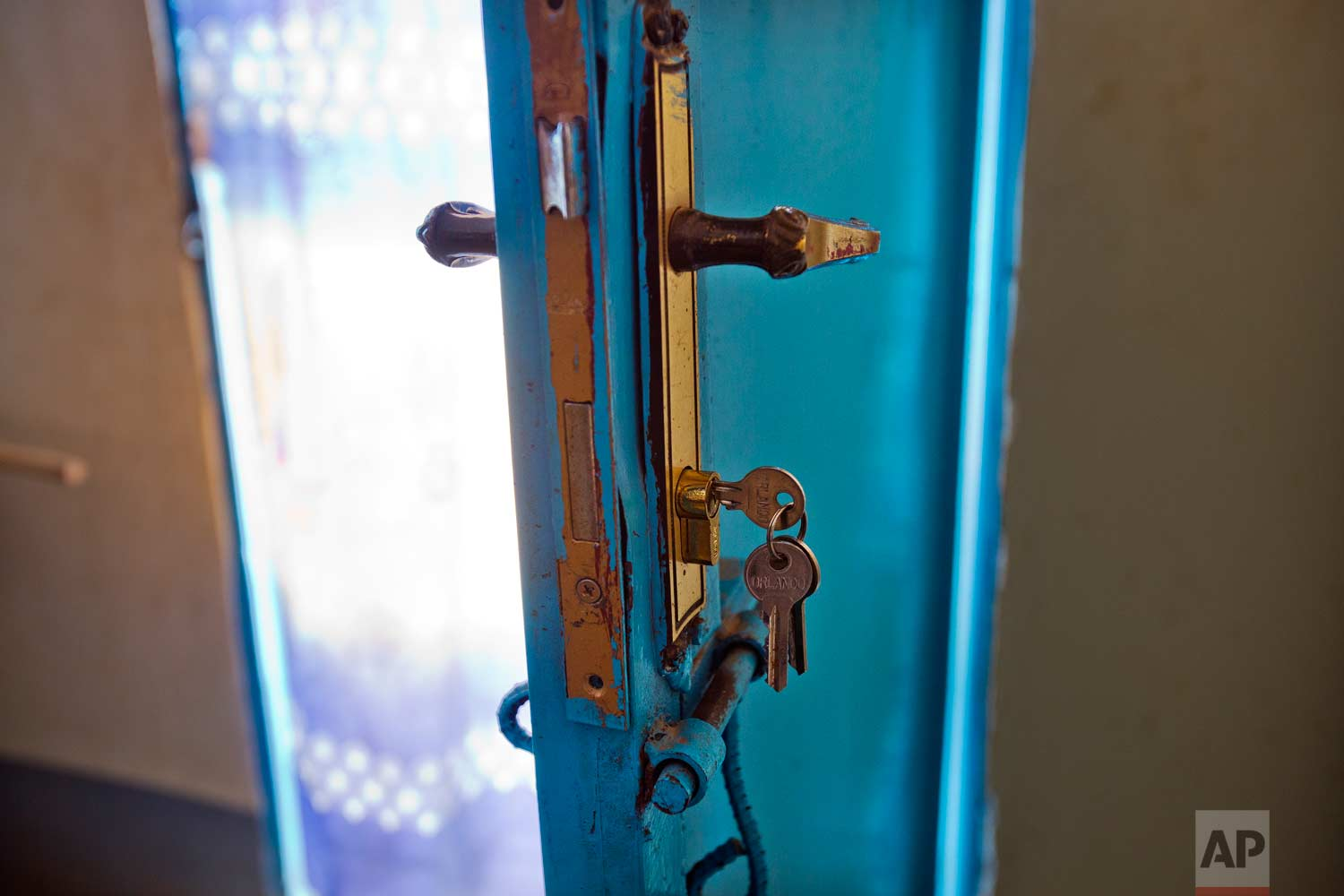A set of keys hangs from a door lock inside the Masaidizi Health Center in Lubumbashi, Democratic Republic of the Congo on Tuesday, Aug. 14, 2018. An Associated Press investigation focused in Congo's second city, the copper-mining metropolis of Lubumbashi, discovered that of more than 20 hospitals and clinics visited, all but one detain patients unable to pay their bills. The practice is illegal according to the Congolese penal code. (AP Photo/Jerome Delay)