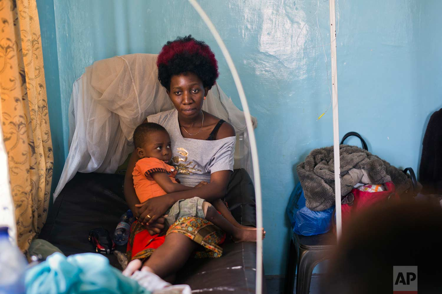 Ado Ntanga, 23, holds her son, Adrielle Nyembwe, 3, who was admitted to the Medicare Policlinic with Sickle Cell Anemia in Lubumbashi, Democratic Republic of the Congo on Wednesday, Aug. 15, 2018. They have both been detained for over a month, unable to pay the $850 medical bill for Adrielle. (AP Photo/Jerome Delay)