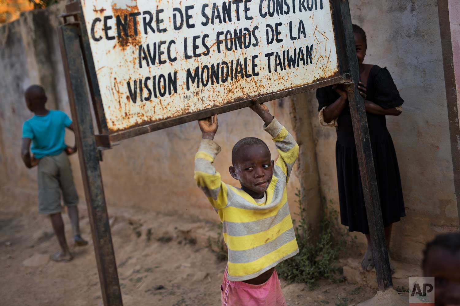 """A child plays under a sign reading, """"health center built with funding from Taiwan World Vision Funds"""" at the Mama Wa Mapendo clinic in Lubumbashi, Democratic Republic of the Congo on Tuesday, Aug. 14, 2018. (AP Photo/Jerome Delay)"""