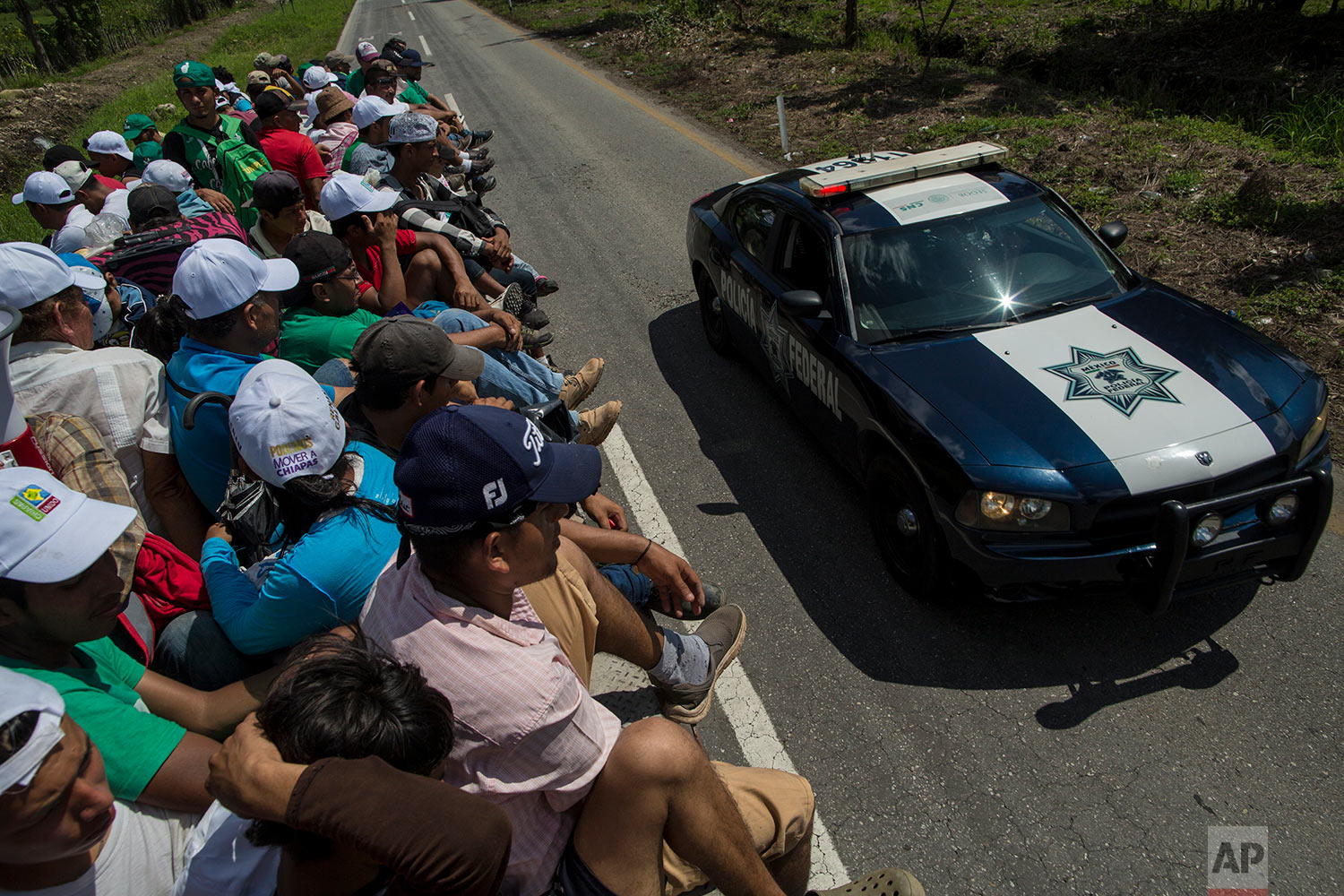 A Mexican police car passes Central American migrants traveling with a caravan to the U.S. as they get a free ride on a tuck bed, as they approach Mapastepec, Mexico, Wednesday, Oct. 24, 2018. (AP Photo/Rodrigo Abd)