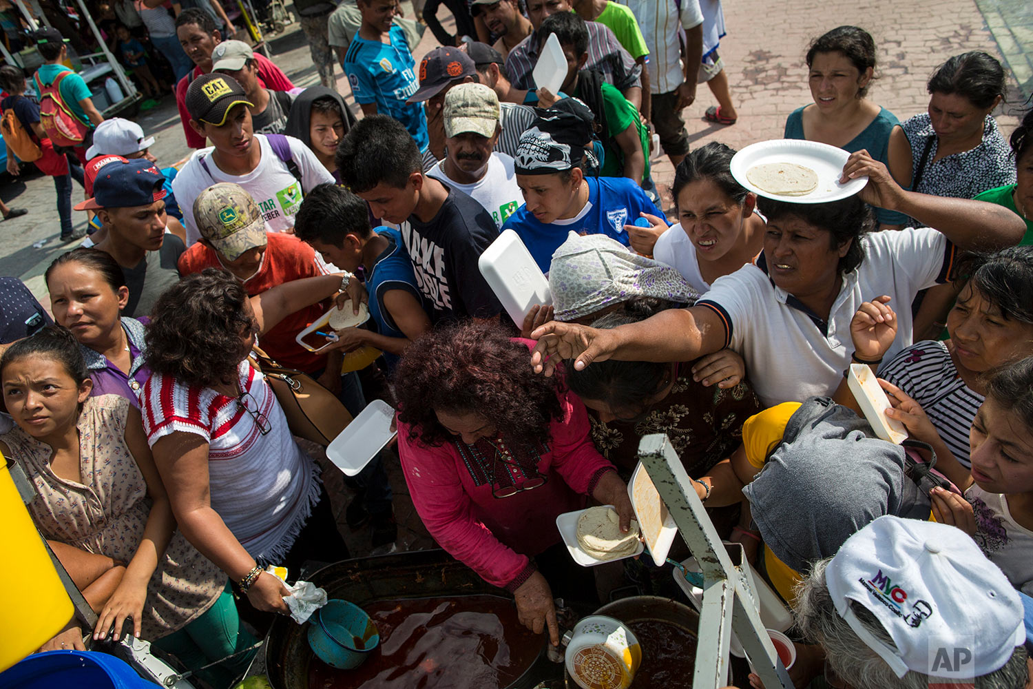 Migrants receive donated food at a makeshift camp set up by a caravan of Central American migrants traveling to the U.S, in Mapastepec, Mexico, Wednesday, Oct. 24, 2018. (AP Photo/Rodrigo Abd)