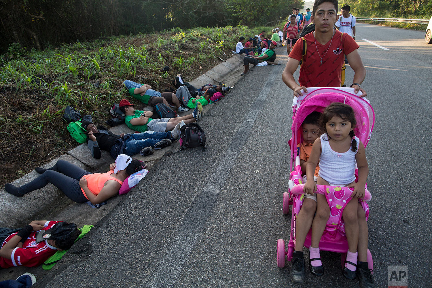 Central American migrant Cristian pushes a carriage occupied by his daughters; Karen, 5, left, and Beiyi, 4, as they make their way to Mapastepec, Mexico, Wednesday, Oct. 24, 2018. (AP Photo/Rodrigo Abd)