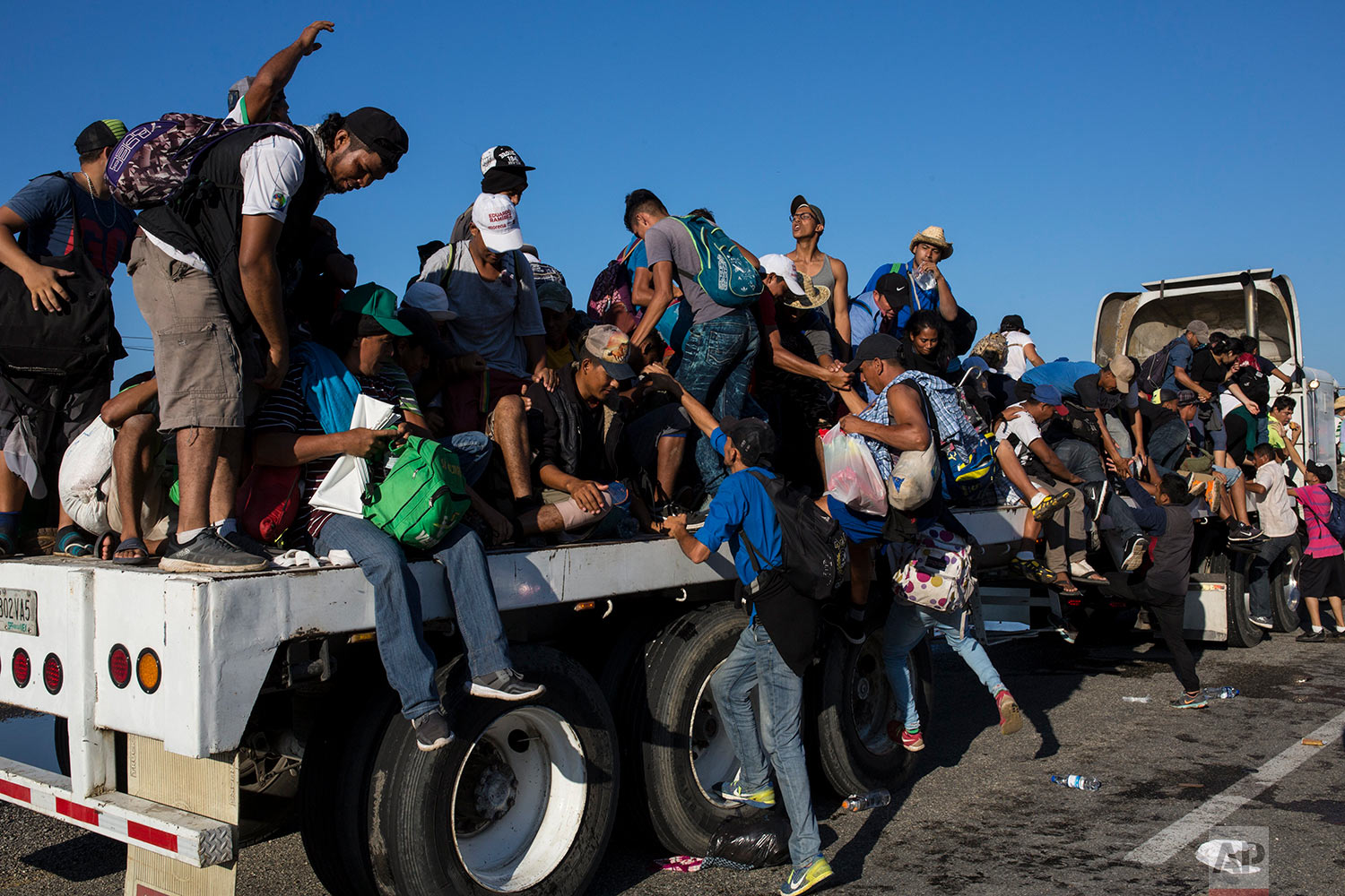Central American migrants traveling with a caravan to the U.S. climb onto to a trailer bed, hitching a ride to Pijijiapan, Mexico, Thursday, Oct. 25, 2018. (AP Photo/Rodrigo Abd)