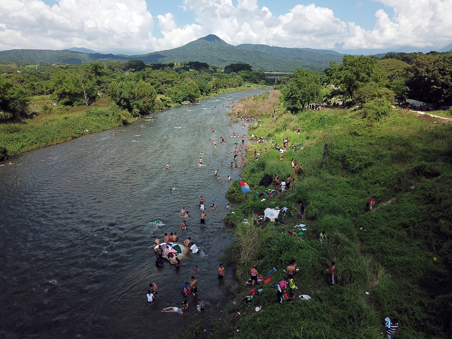 Honduran migrants take a bath in a river in Pijijiapan, Mexico, Thursday, Oct. 25, 2018. (AP Photo/Rodrigo Abd)