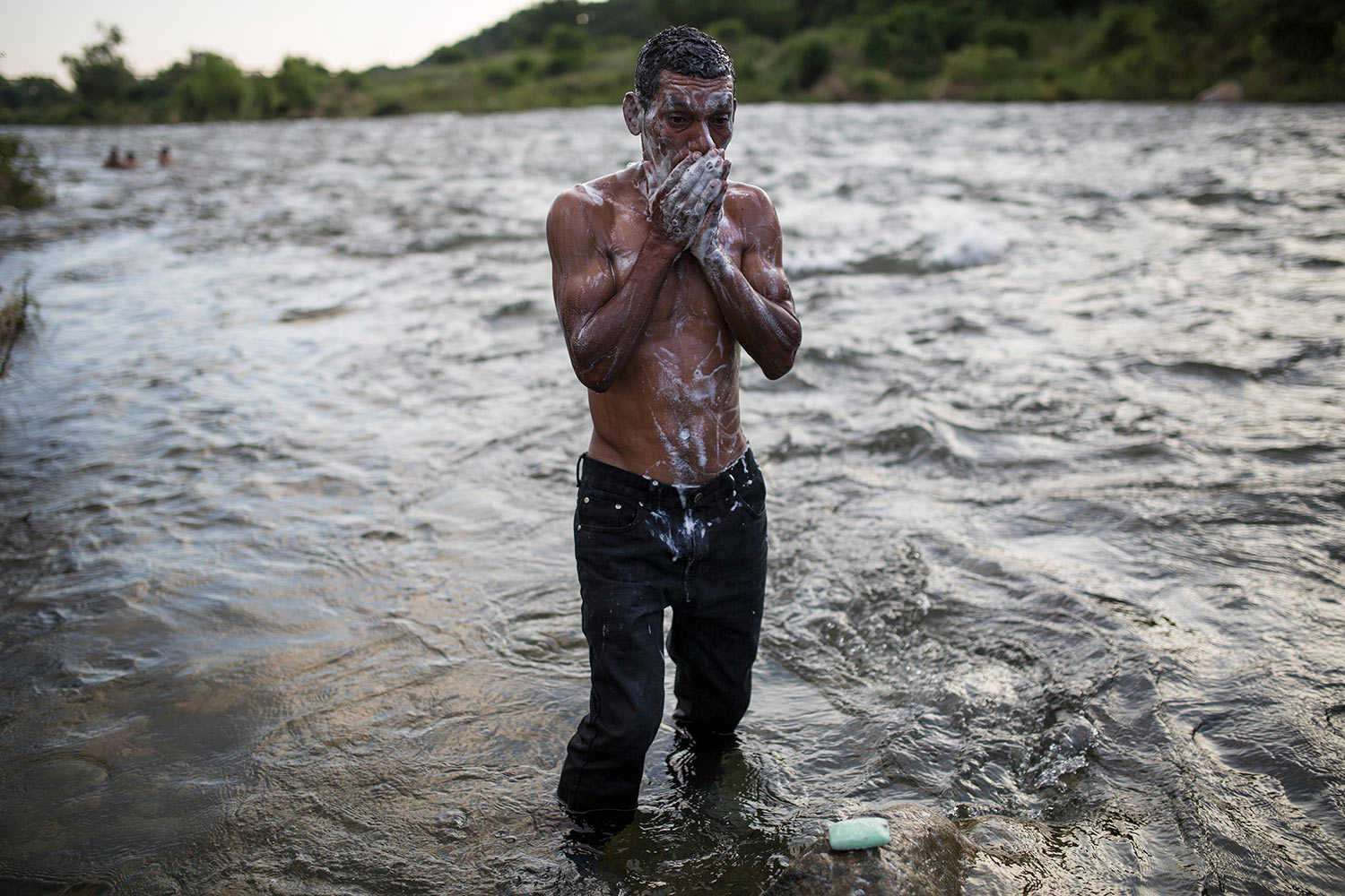 A Honduran migrant takes a bath in a river in Pijijiapan, Mexico, Thursday, Oct. 25, 2018. (AP Photo/Rodrigo Abd)
