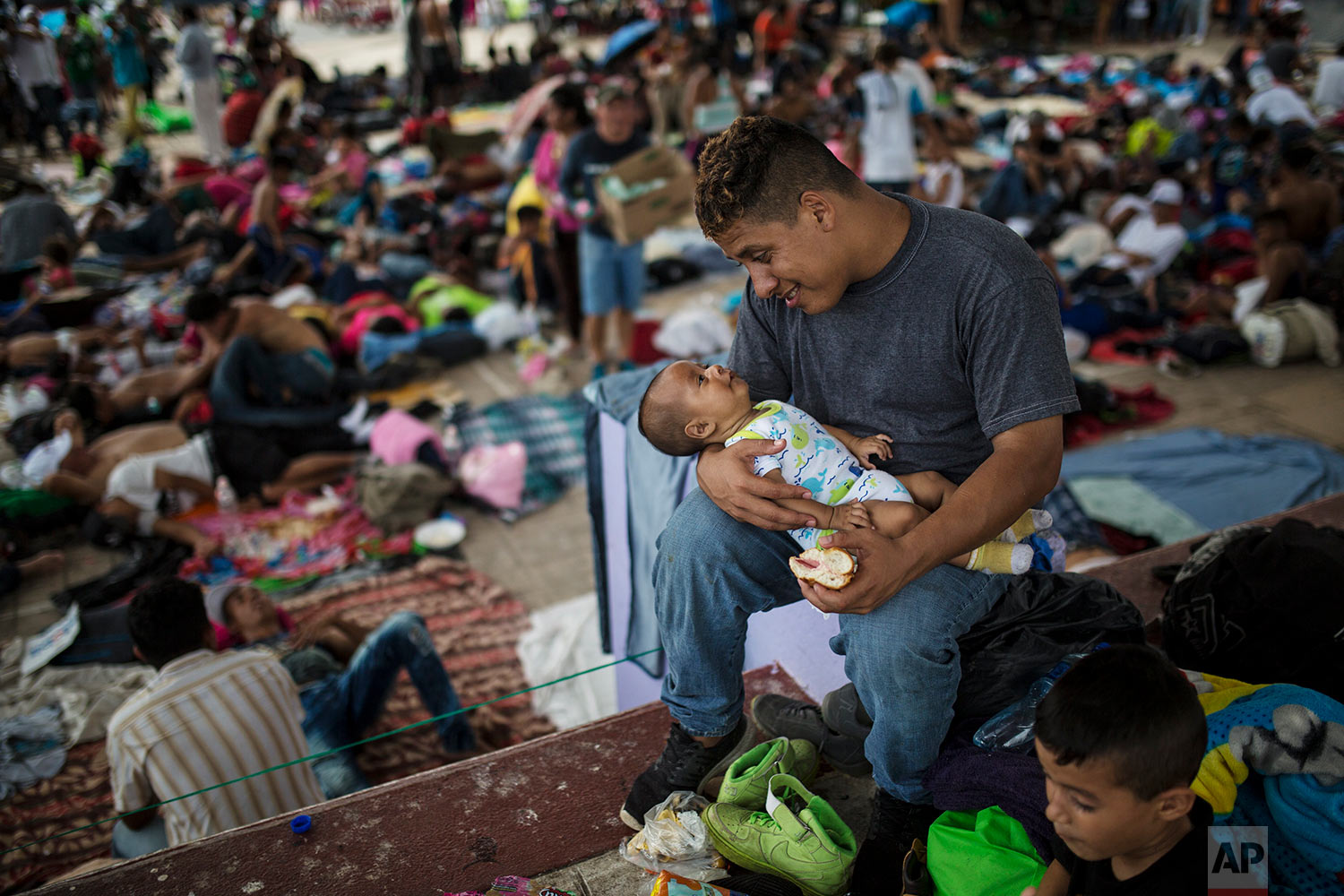 Jose Luis Ramos, a Honduran migrant traveling to the U.S. with a caravan, plays with his 3-month-old son Froilan in the central square of Mapastepec, Mexico, Wednesday, Oct. 24, 2018. (AP Photo/Rodrigo Abd)