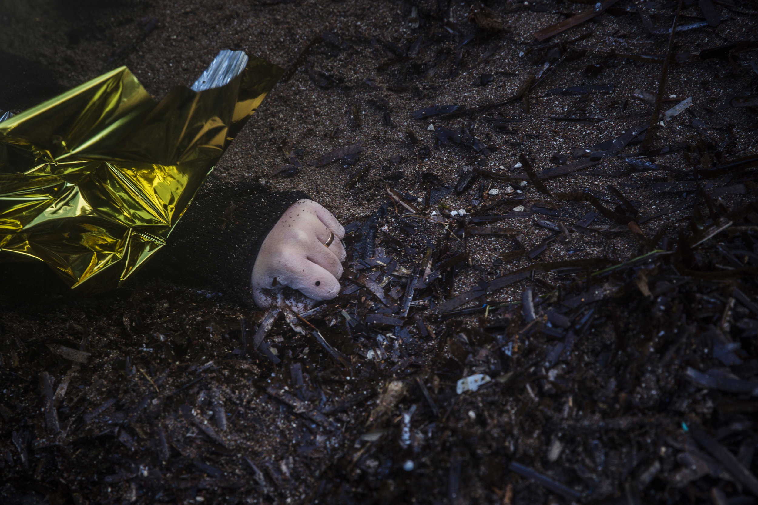 This Sunday, Nov. 1, 2015 photo shows the hand of an unidentified woman wearing a wedding ring on a beach after her body washed up on the shoreline at the village of Skala, on the Greek island of Lesbos. (AP Photo/Santi Palacios)