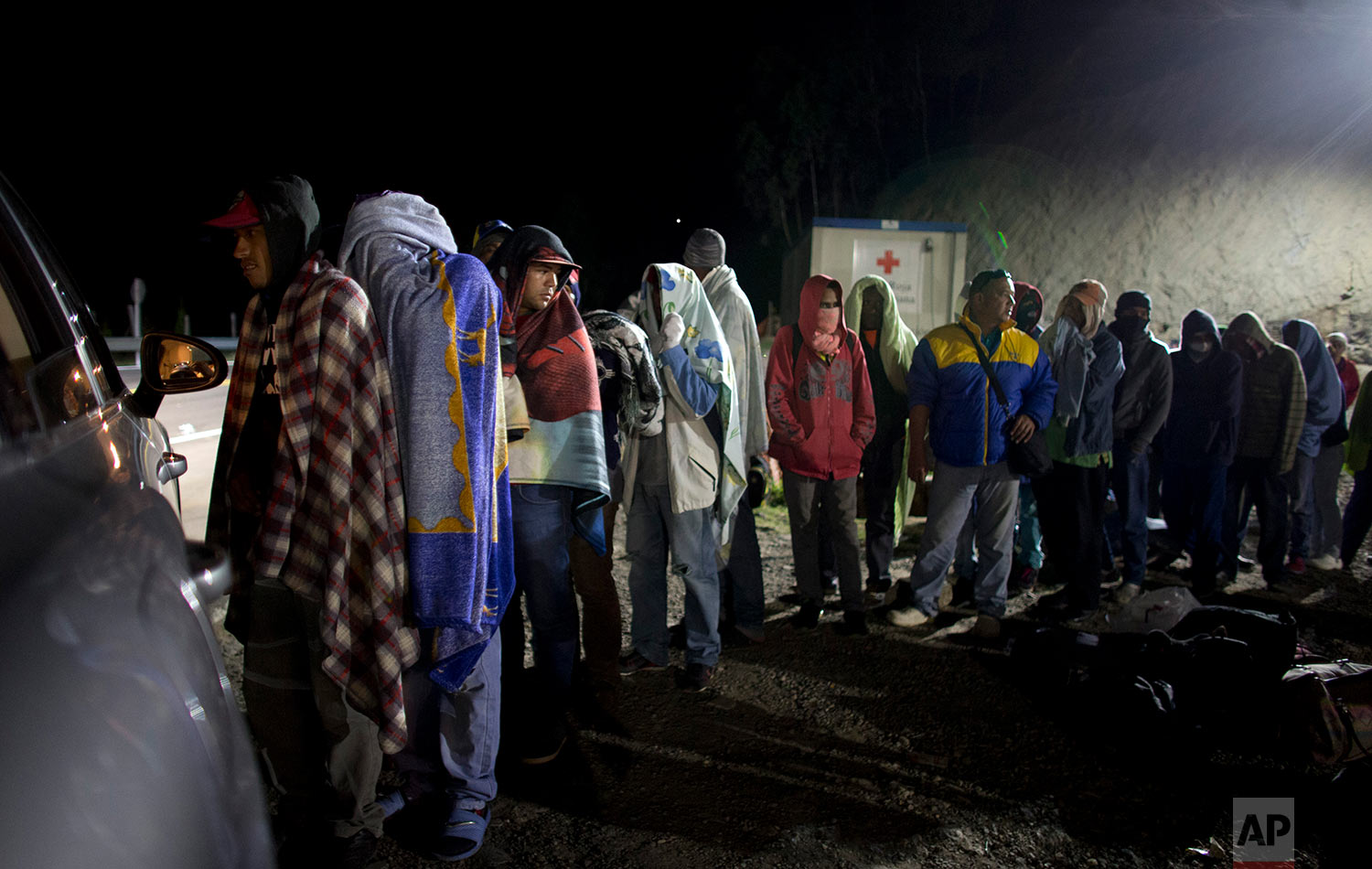 In this Friday, Aug. 31, 2018 photo, Venezuelan migrants line up for free bread and coffee, donated by a Colombian family from their car, at a gas station in Pamplona, Colombia. (AP Photo/Ariana Cubillos)