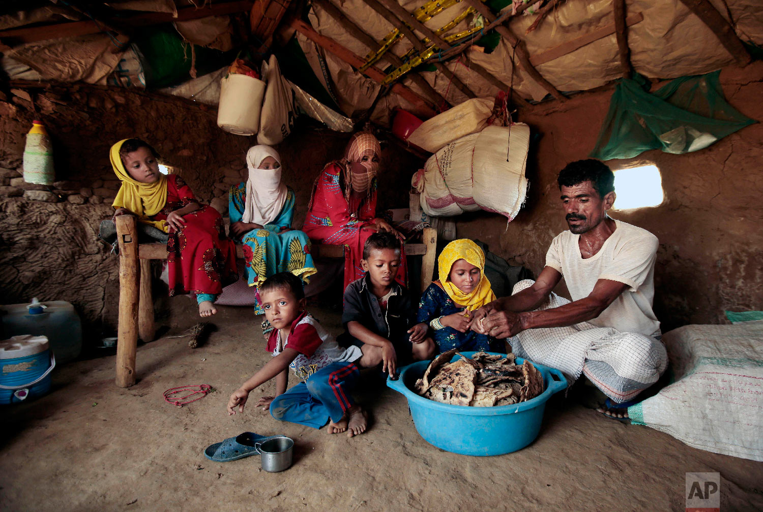 Yahia Hussein feeds his children moldy bread in their shelter, in Aslam, Hajjah, Yemen. (AP Photo/Hani Mohammed)