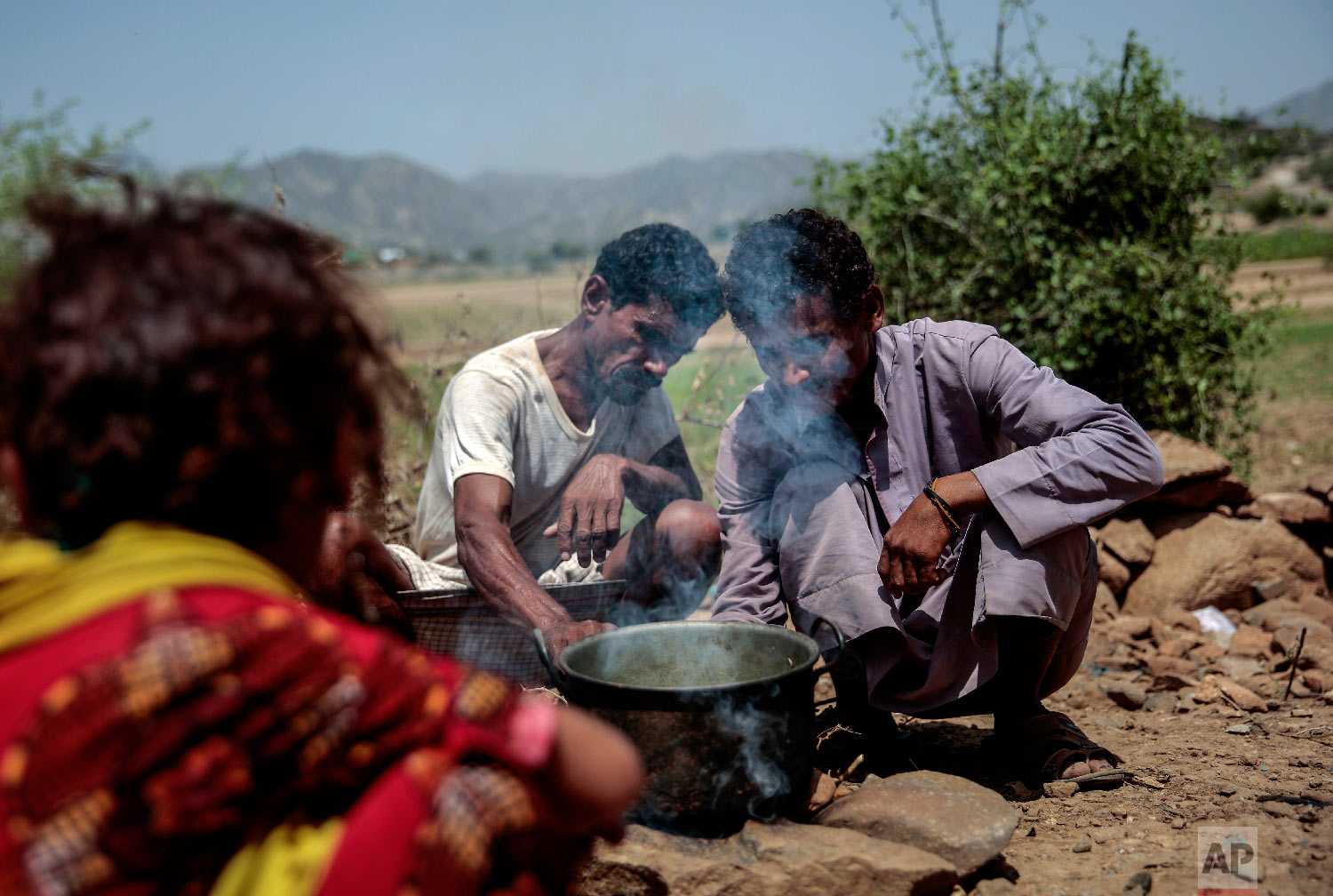Men cook Halas for their children, a climbing vine of green leaves, in Aslam, Hajjah, Yemen. The leaves are made into green paste and used to be a traditional side dish, but at times of extreme poverty, it becomes the main meal. (AP Photo/Hani Mohammed)