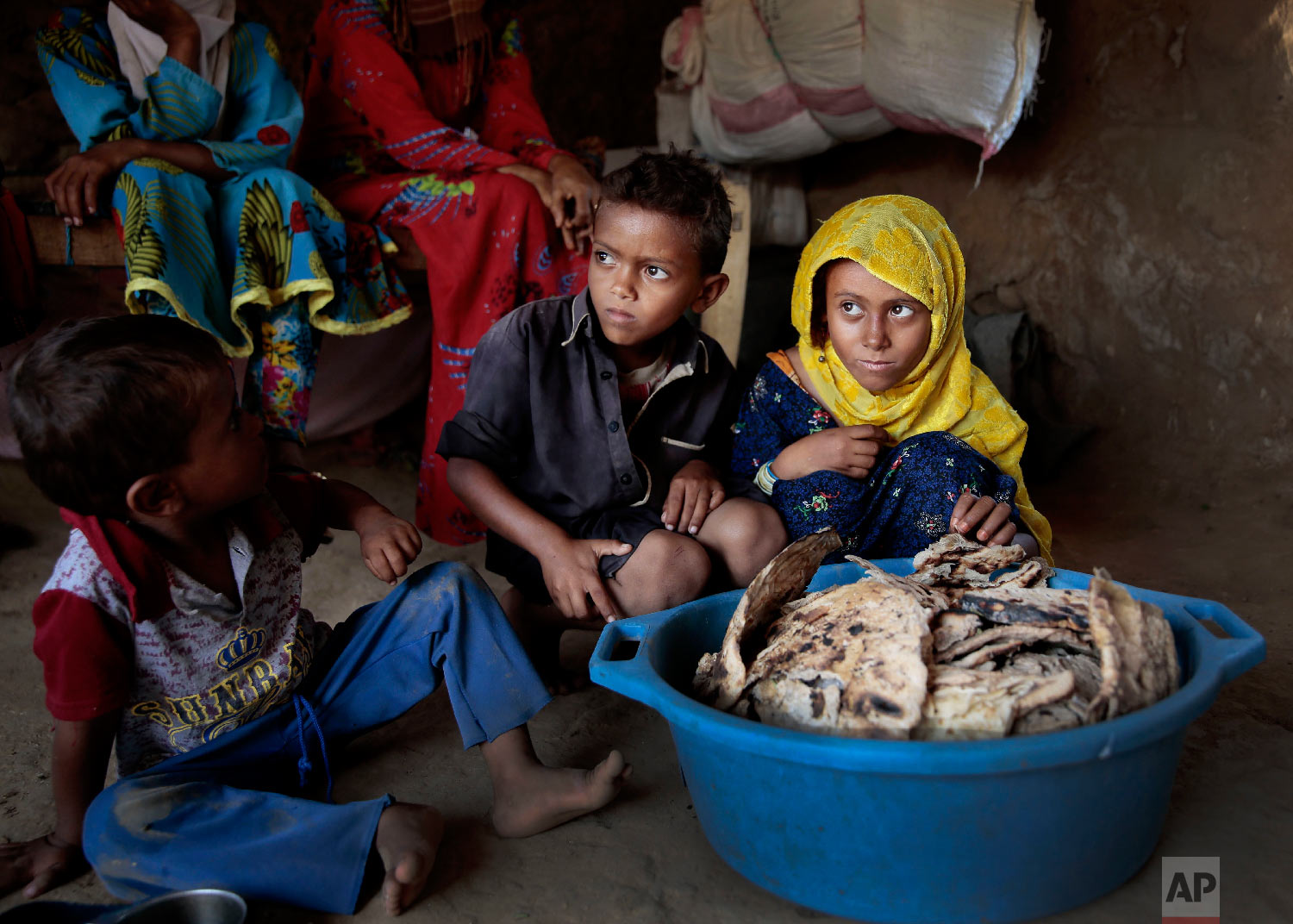 Children sit in front of moldy bread in their shelter, in Aslam, Hajjah, Yemen. (AP Photo/Hani Mohammed)