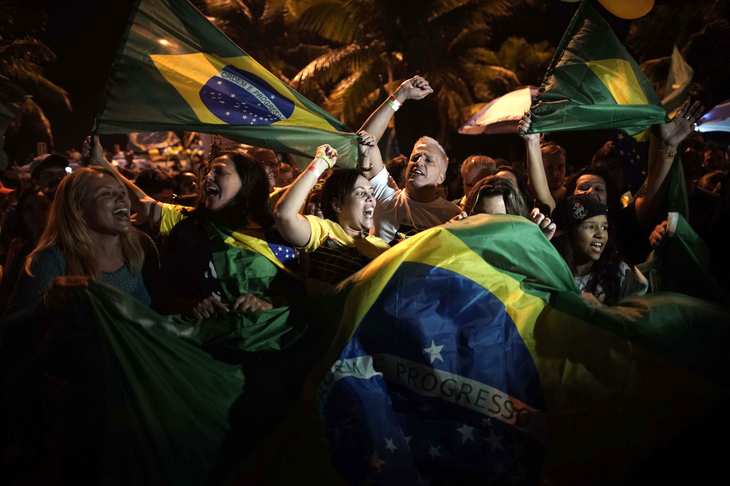 Supporters of Jair Bolsonaro celebrate in front of his residence in Rio de Janeiro, Brazil, Sunday, Oct. 28, 2018. The far-right congressman took a commanding lead in the race for Brazil's presidency, as voters apparently looked past warnings that the former army captain would erode democracy and embraced a chance for radical change after years of turmoil. (AP Photo/Leo Correa)