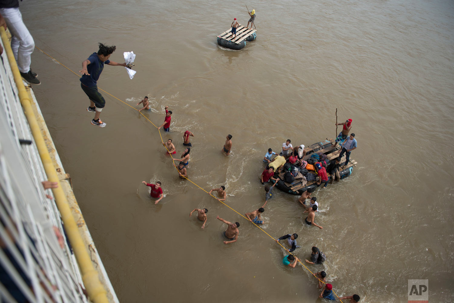Migrants tired of waiting to cross into Mexico jump from a border bridge into the Suchiate River in Tecun Uman, Guatemala, Friday, Oct. 19, 2018, as a second caravan makes its way to the U.S. Some of the migrants traveling in a mass caravan towards the U.S.-Mexico border organized a rope brigade to ford its muddy waters. (AP Photo/Oliver de Ros)