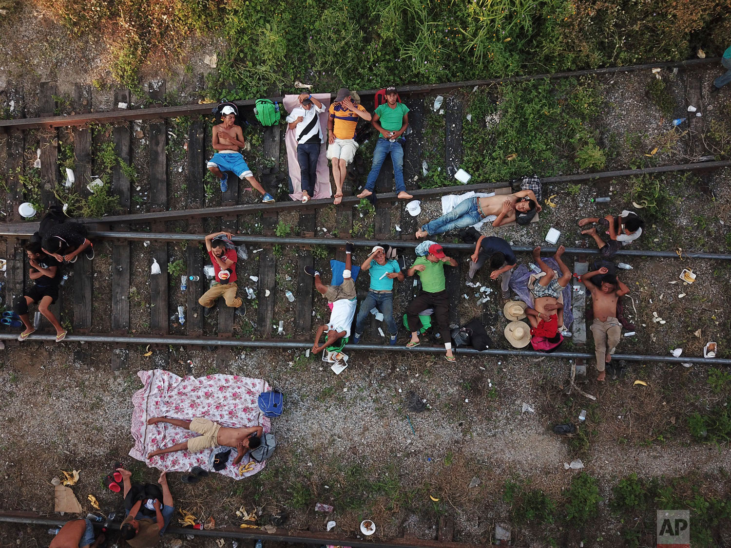 Migrants traveling in a caravan to the U.S. border rest on the railroad tracks in Arriaga, Mexico, Friday, Oct. 26, 2018. Many migrants said they felt safer traveling and sleeping with several thousand strangers in unknown towns rather than hiring a smuggler or trying to make the trip alone. (AP Photo/Rodrigo Abd)