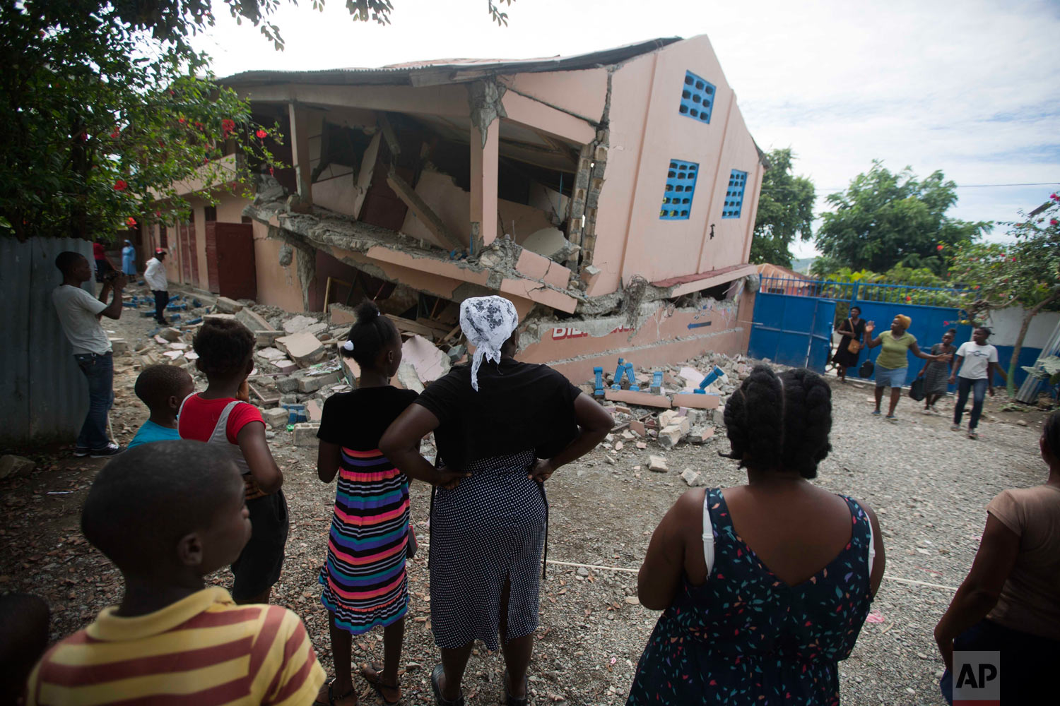 Residents look at a collapsed school after a magnitude 5.9 earthquake hit the night before in Gros Morne, Haiti, Oct. 7, 2018. The quake killed at least 11 people and left dozens injured. (AP Photo/Dieu Nalio Chery)