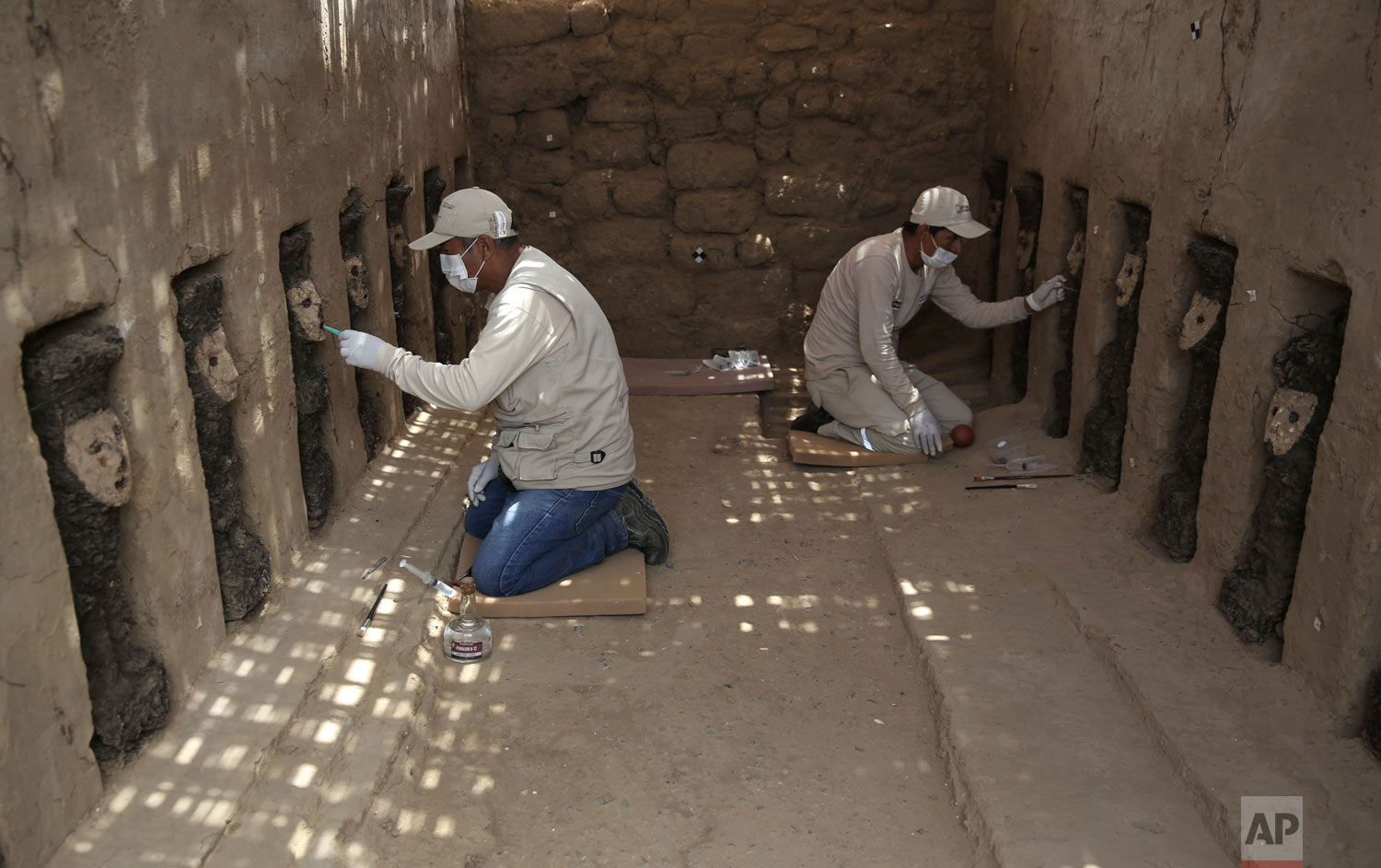 Archaeologists clean the clay masks of wooden idols that protect the entrance to a ceremonial center in the pre-Columbian adobe city of Chan Chan, near Trujillo, Peru, Monday, Oct. 22, 2018. Peru's Ministry of Culture presented the wooden idols as part of a series of important archaeological discoveries in the Chan Chan citadel belonging to the ancient Chimu empire who were conquered by the Incas in the late 15th century. (AP Photo/Martin Mejia)