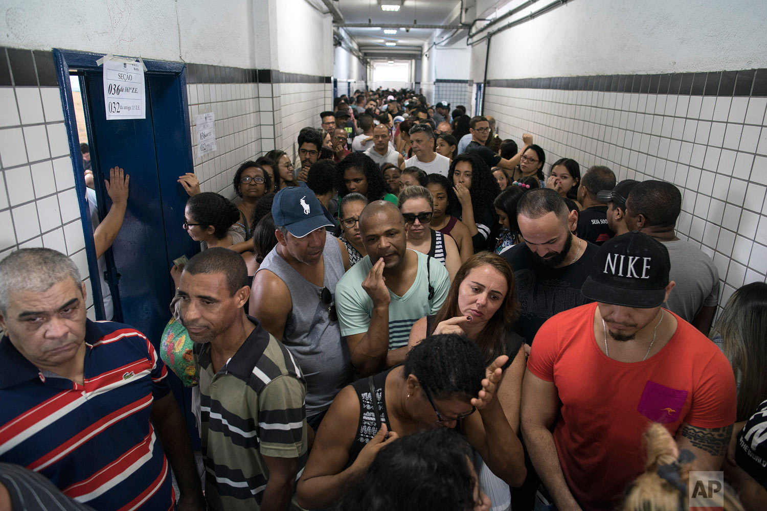 People wait in line to vote in the general election at a polling station in the Mare Complex slum in Rio de Janeiro, Brazil, Oct. 7, 2018. Brazilians choose among 13 candidates for president Sunday in one of the most unpredictable and divisive elections in decades. (AP Photo/Leo Correa)