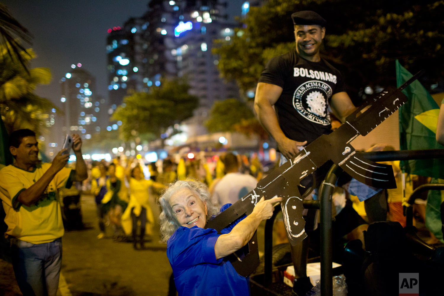 A supporter of presidential candidate Jair Bolsonaro poses for a photo with an oversized, fake rifle, as she celebrates the election runoff results in Rio de Janeiro, Brazil, Oct. 28, 2018. Brazil's Supreme Electoral Tribunal declared the right-leaning congressman the next president of Latin America's biggest country. (AP Photo/Silvia Izquierdo)