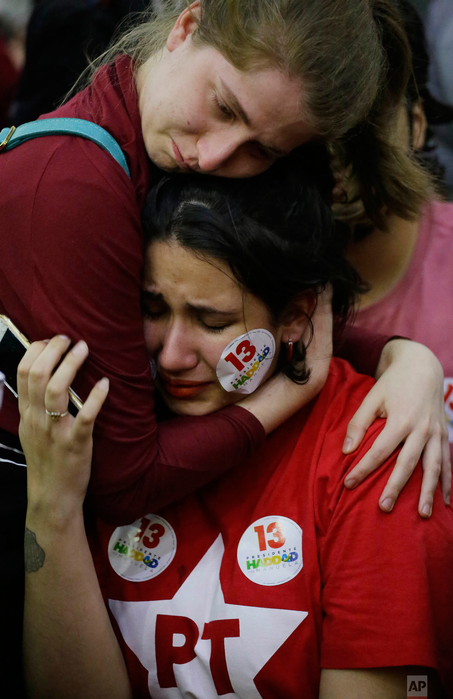 A supporter of Workers' Party presidential candidate Fernando Haddad embraces a fellow distraught supporter, after learning that rival Jair Bolsonaro was declared the winner in the presidential runoff election, in Sao Paulo, Brazil, Oct. 28, 2018. Addressing supporters in Sao Paulo, Haddad did not concede or even mention Bolsonaro by name. Instead, his speech was a promise to resist. (AP Photo/Nelson Antoine)