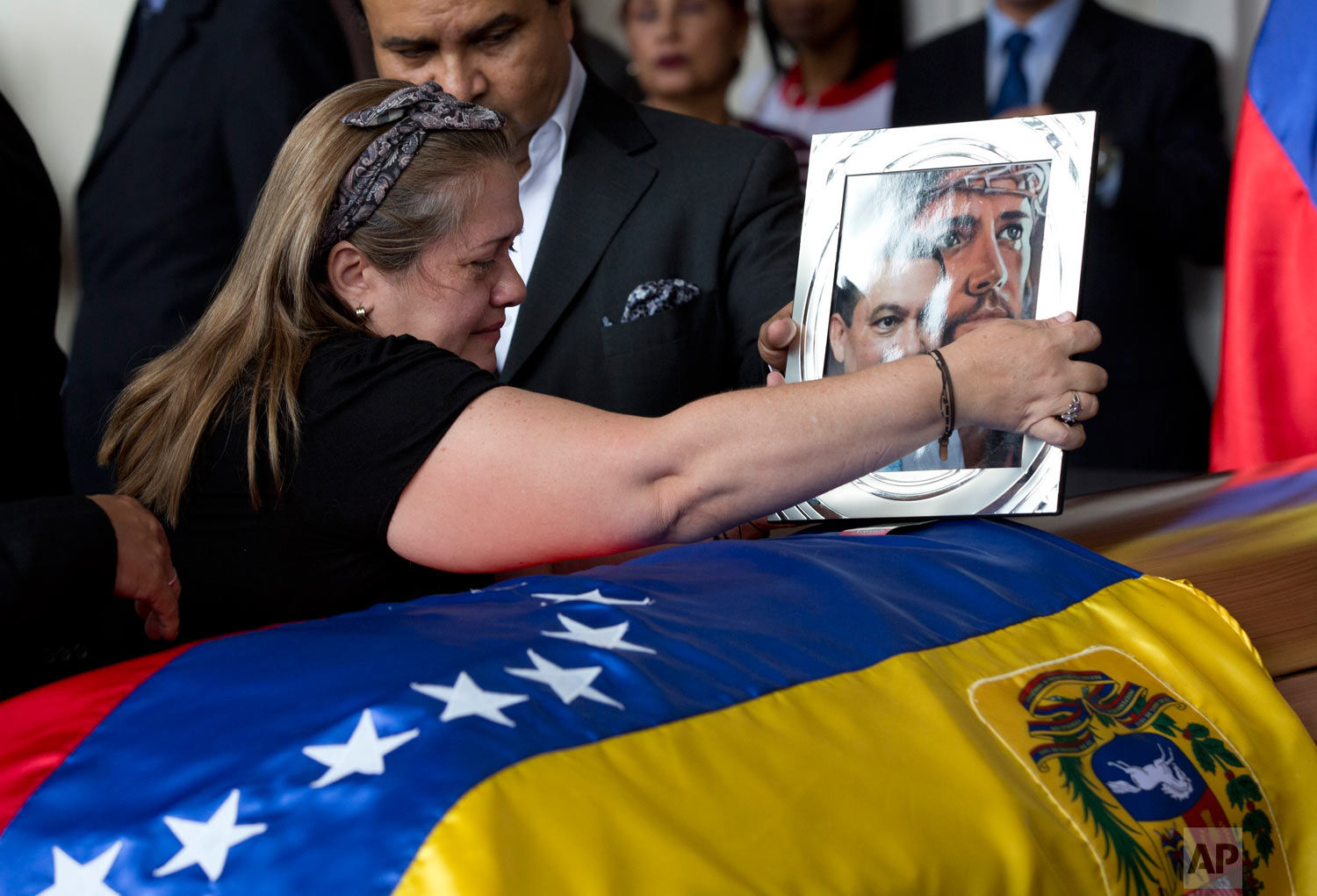 Luz Alban, the sister of opposition activist Fernando Alban places a portrait of her brother shadowed by an image of Jesus Christ, on his flag-draped casket during a ceremony at the National Assembly headquarters, in Caracas, Venezuela, Oct. 9, 2018. Questions and condemnation of Venezuela's leadership poured in following the suspicious death of Alban who authorities say evaded justice by throwing himself from the 10th floor of a police building. (AP Photo/Ariana Cubillos)