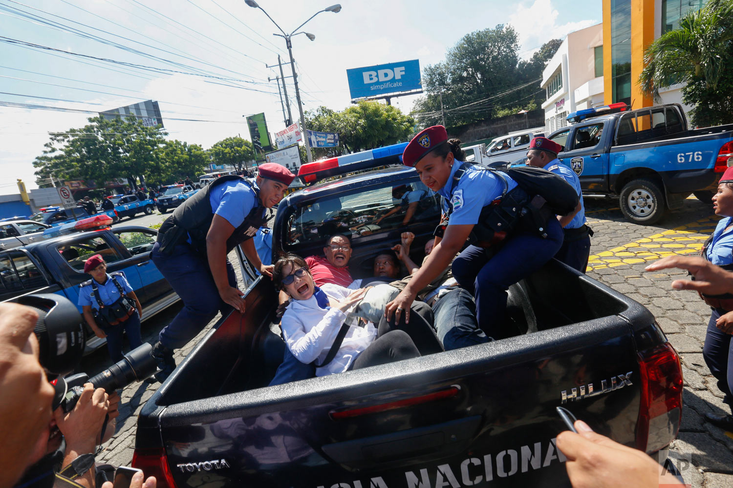 """Anti-government protesters are arrested and taken away by police as security forces disrupt their march, coined """"United for Freedom,"""" in Managua, Nicaragua, Oct. 14, 2018. Anti-government protests calling for President Daniel Ortega's resignation are ongoing since April, triggered by a since-rescinded government plan to cut social security pensions. Ortega said opponents will have to wait until his term ends in 2021. (AP Photo/Alfredo Zuniga)"""