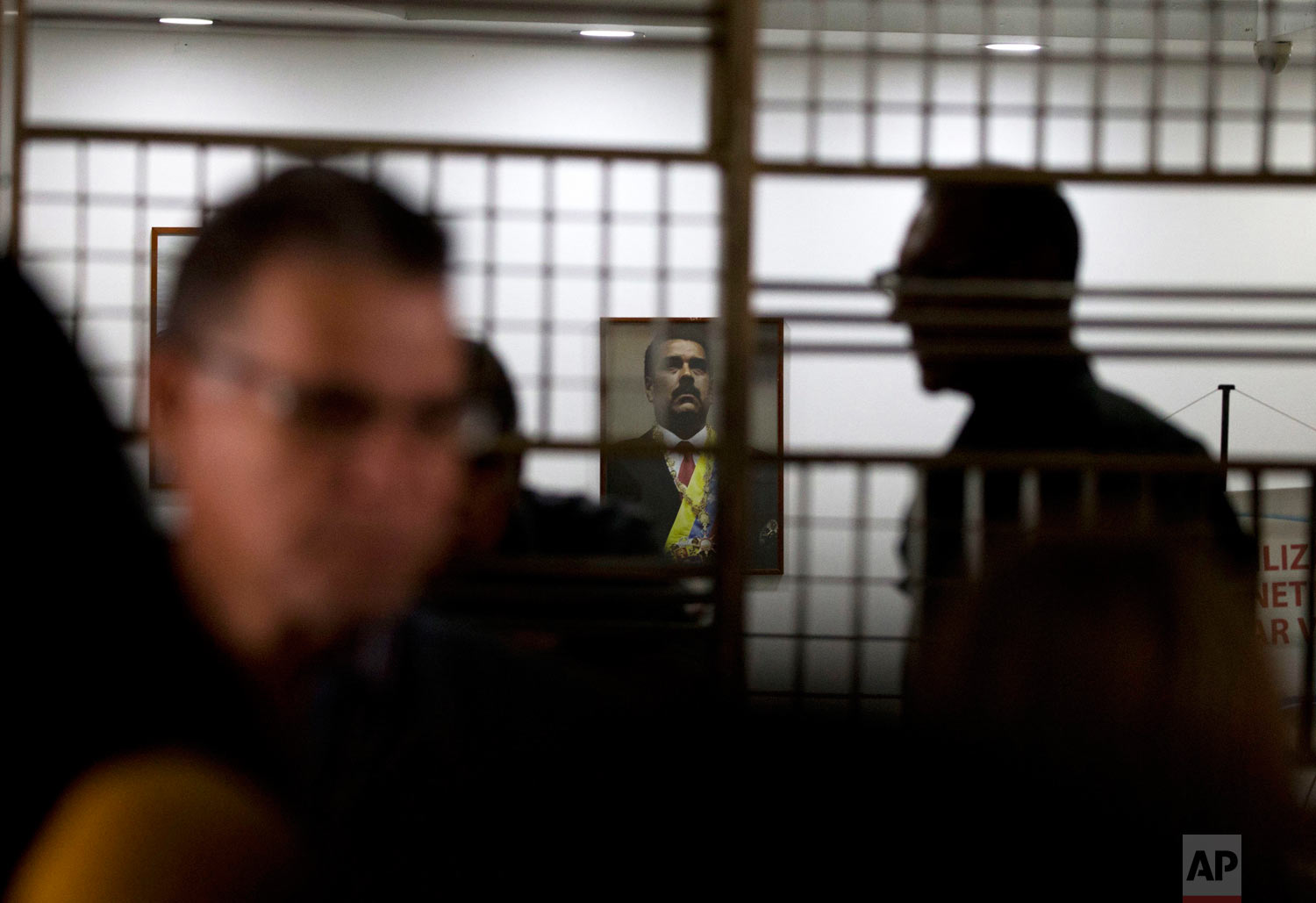 An image of Venezuela's President Nicolas Maduro hangs above the main desk at the Labor Ministry as workers demanding better wages protest outside the building, in Caracas, Venezuela, Oct. 5, 2018. (AP Photo/Fernando Llano)