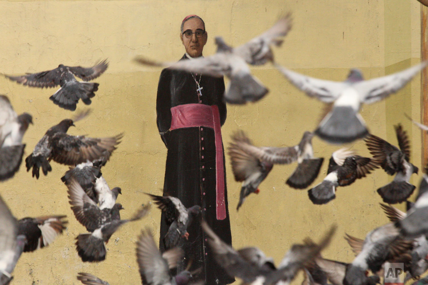 Pigeons fly in front of a mural of Archbishop Oscar Arnulfo Romero, on a wall of the Metropolitan Cathedral in San Salvador, El Salvador, Oct. 3. 2018. Romero will be canonized in Rome by Pope Francis on Sunday, Oct. 14th. Romero was assassinated in 1980 while celebrating Mass by a gunman hired by right-wing death squads. (AP Photo/Salvador Melendez)