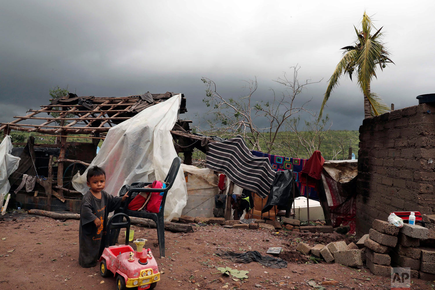 A child stands near his home damaged by Hurricane Willa in Escuinapa, Mexico, Oct. 24, 2018. There were no immediate reports of deaths or missing people, but Willa's strong winds damaged a hospital, knocked out power, toppled wood-shack homes and ripped metal roofing off other houses in the Sinaloa state municipality of Escuinapa when it came ashore. (AP Photo/Marco Ugarte)