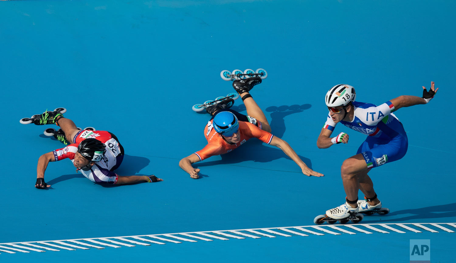 In this photo provided by the OIS/IOC, Italy's Vincenzo Maiorca takes the lead as Taiwan's Chiawei Chang, center, and The Netherland's Merijn Scheperkamp fall during the Roller Speed Skating Men's Combined Speed Event during the Youth Olympic Games in Buenos Aires, Argentina, Monday, Oct. 8, 2018. (Simon Bruty/OIS/IOC via AP)