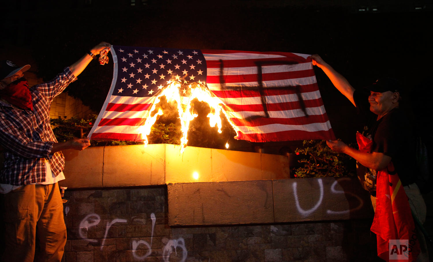 People burn a U.S. flag outside the U.S. embassy to protest in favor of the migrant caravan stuck on the Guatemala-Mexico border, in Tegucigalpa, Honduras, Oct. 19, 2018. (AP Photo/Fernando Antonio)