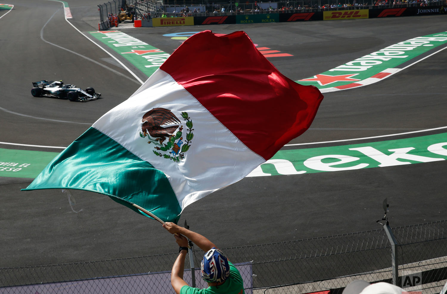 Mercedes driver Lewis Hamilton, from Britain, drives in a practice run for the upcoming Formula One Mexico Grand Prix auto race, as a fan waves a Mexican flag at the Hermanos Rodriguez racetrack in Mexico City, Oct. 26, 2018. (AP Photo/Marco Ugarte)
