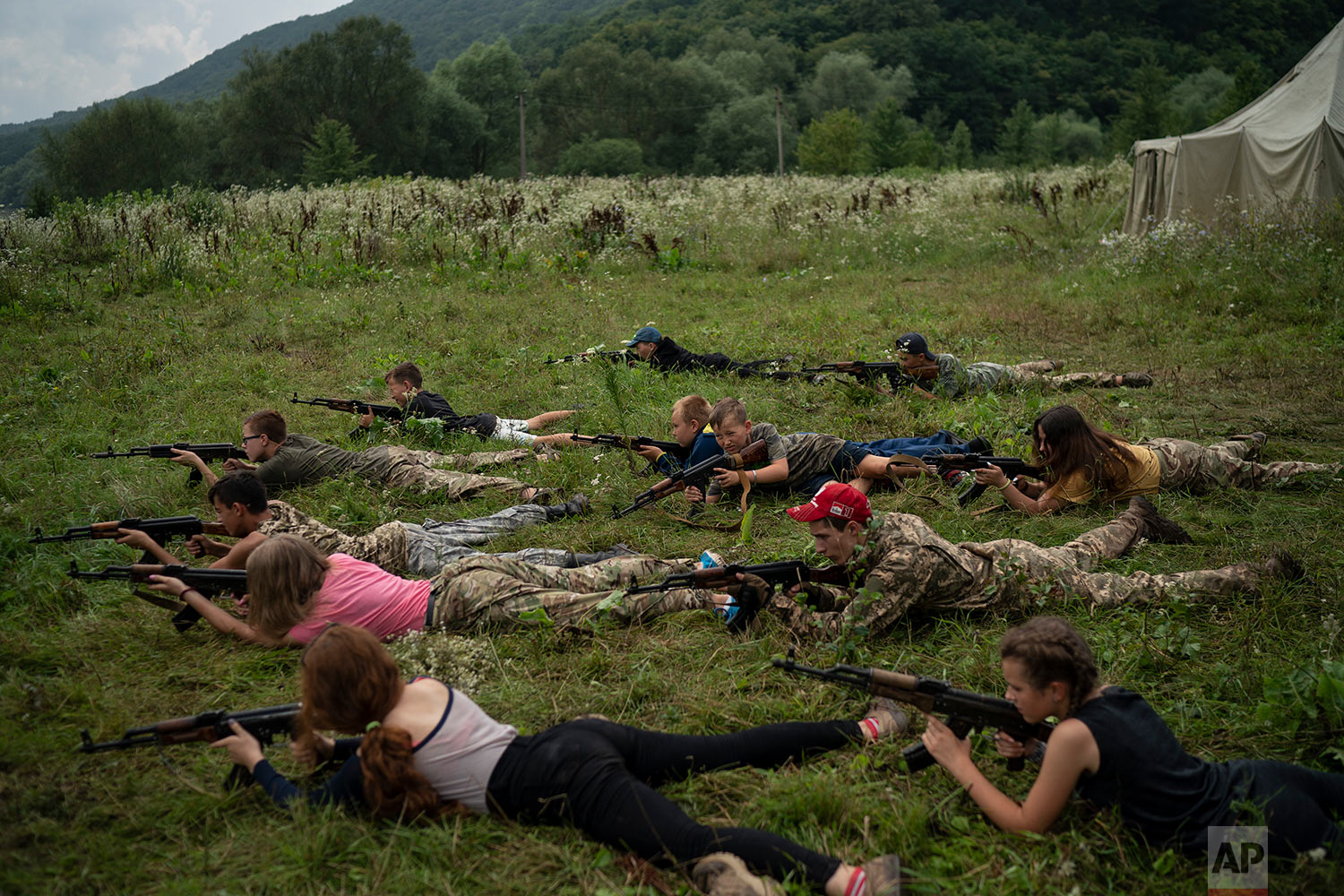 "Young participants of the ""Temper of will"" summer camp, organized by Svoboda party, lay on the ground with their AK-47 riffles during a tactical exercise on July 28, 2018, in a village near Ternopil, Ukraine. (AP Photo/Felipe Dana)"