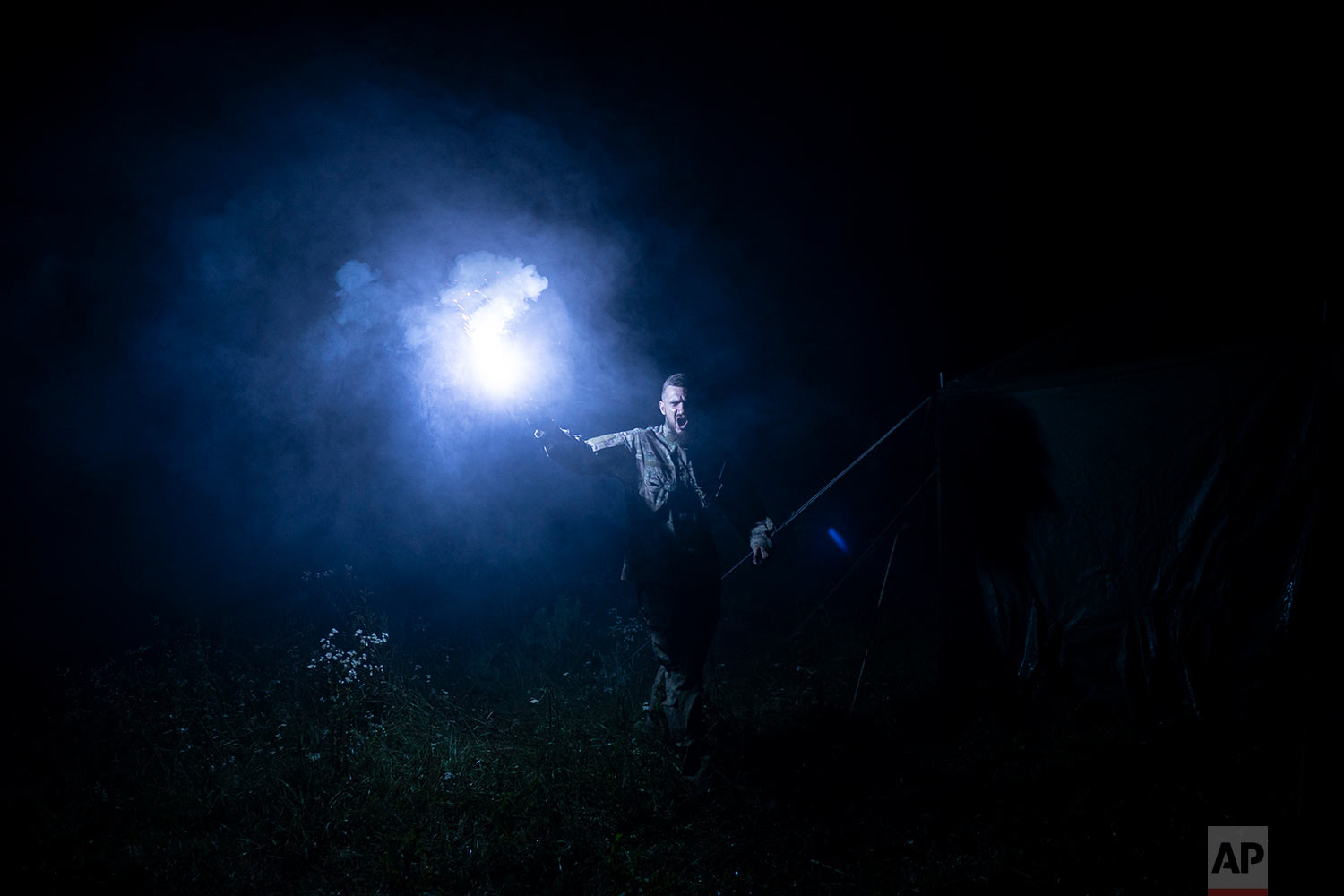 "Instructor Georgiy Barylenko, holds a flare as he instructs young participants of the ""Temper of will"" summer camp, organized by the nationalist Svoboda party, during a night drill on July 29, 2018, in a village near Ternopil, Ukraine. (AP Photo/Felipe Dana)"