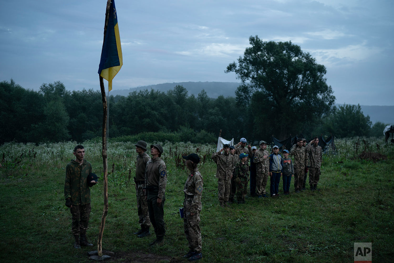 "Young participants and instructors of the ""Temper of will"" summer camp, organized by the nationalist Svoboda party, stand in formation as they sing the national anthemn on July 28, 2018, in a village near Ternopil, Ukraine. Earlier this year, the Ministry of Youth and Sports earmarked 4 million hryvnias (about $150,000) to fund some of the youth camps among the dozens built by the nationalists. (AP Photo/Felipe Dana)"