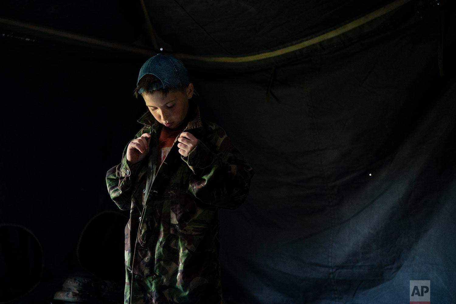 "A young participant of the ""Temper of will"" summer camp, organized by the nationalist Svoboda party, buttons up a camouflage shirt as he prepares for an exercise on July 27, 2018, in a village near Ternopil, Ukraine. Campers as young as 8 years old practice using assault rifles. They are taught to shoot to kill Russians and their sympathizers. (AP Photo/Felipe Dana)"