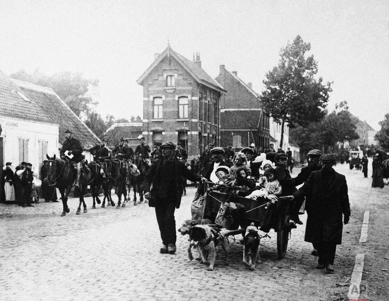 In this Oct. 14, 1914 photo, Belgian civilians and a cavalry detail move out of the pathway of the German advance during World War One in Antwerp, Belgium. (AP Photo)