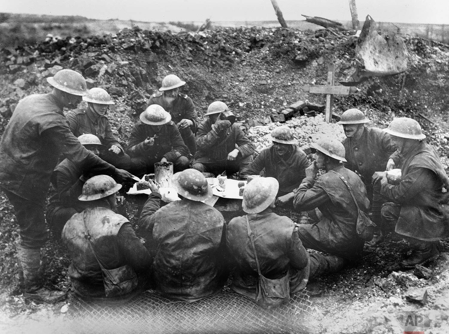 In this undated photo, Allied soldiers eat and drink in a shell hole in France during World War One. (AP Photo)