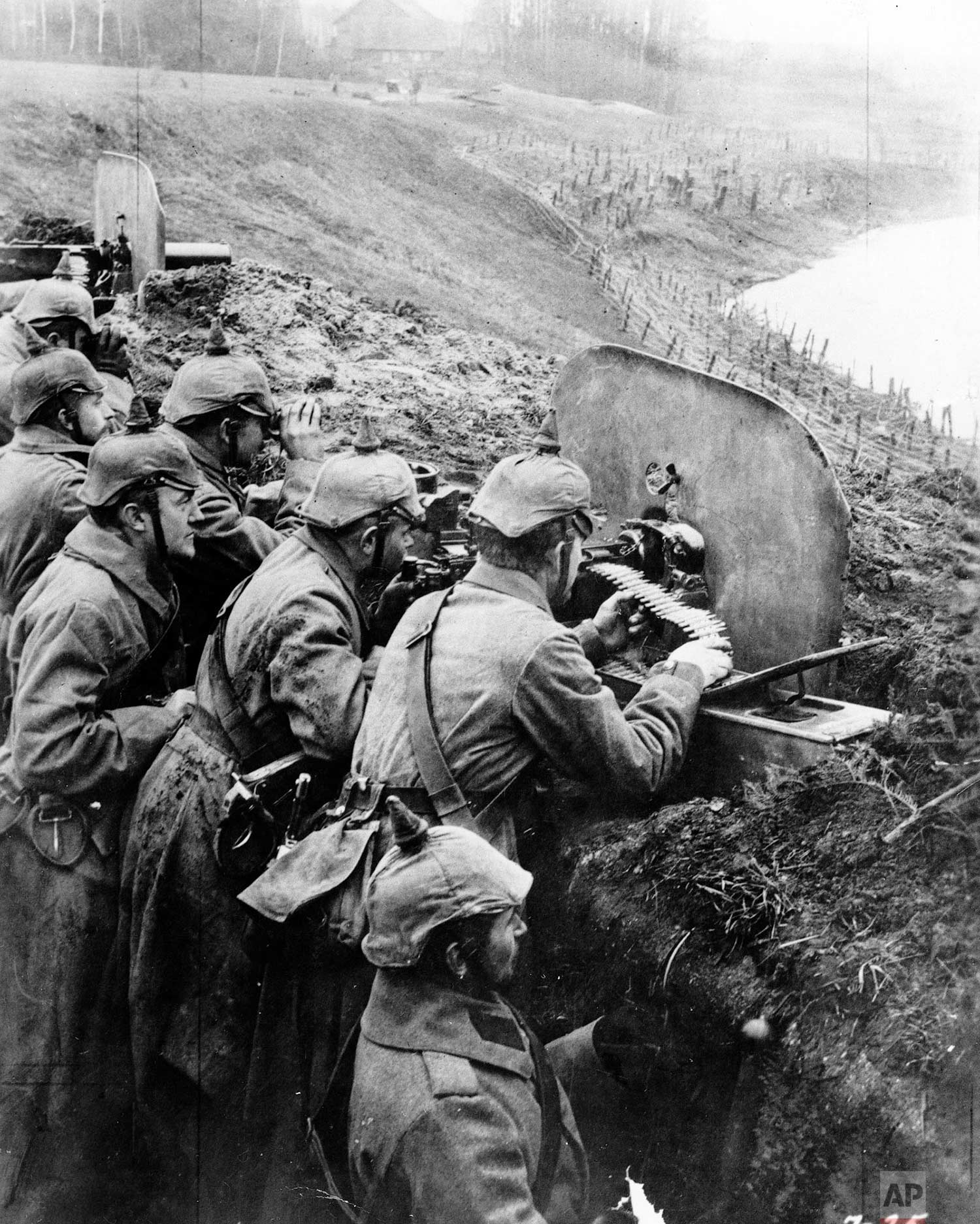 In this 1916 photo, German troops man a machine gun post from a trench at the Vistula River in Russia during World War One. (AP-Photo)