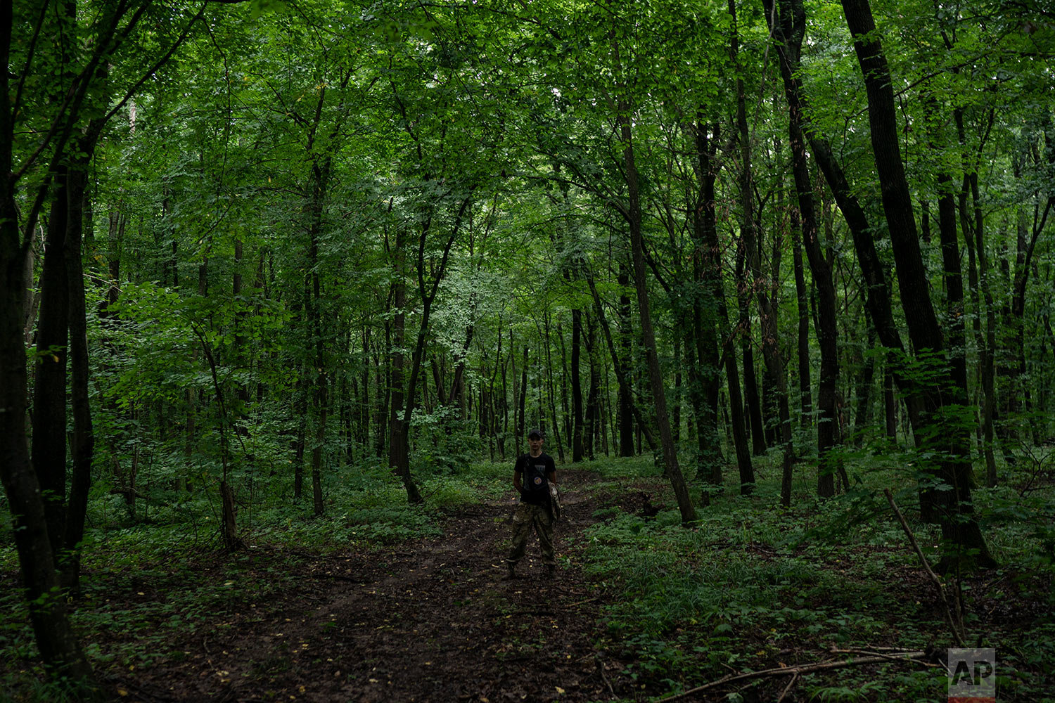 "A member of Sokil (Falcon), the youth wing of the nationalist Svoboda party, stands in a forest as he guides participants to the ""Temper of will"" summer camp on July 27, 2018, in a village near Ternopil, Ukraine. (AP Photo/Felipe Dana)"