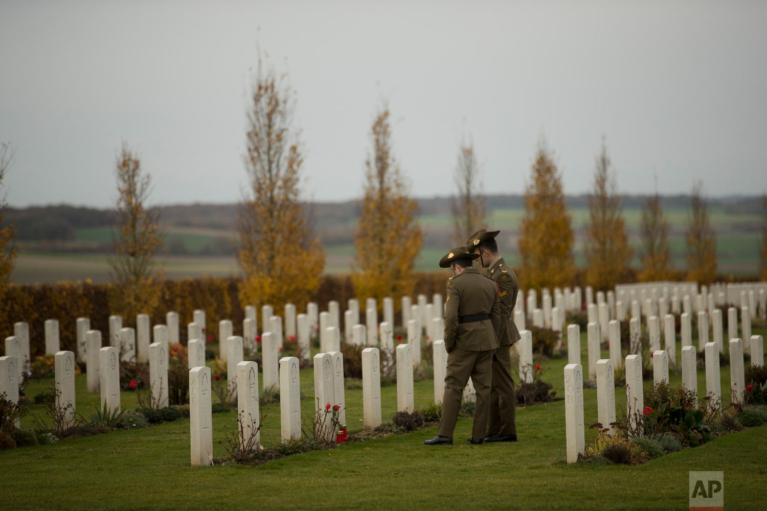 Two Australian soldiers walk along graves prior to an Armistice ceremony marking 100 years since the end of the World War I, at the Australian National Memorial in Villers-Bretonneux, France, Sunday, Nov. 11, 2018. (AP Photo/Francisco Seco)
