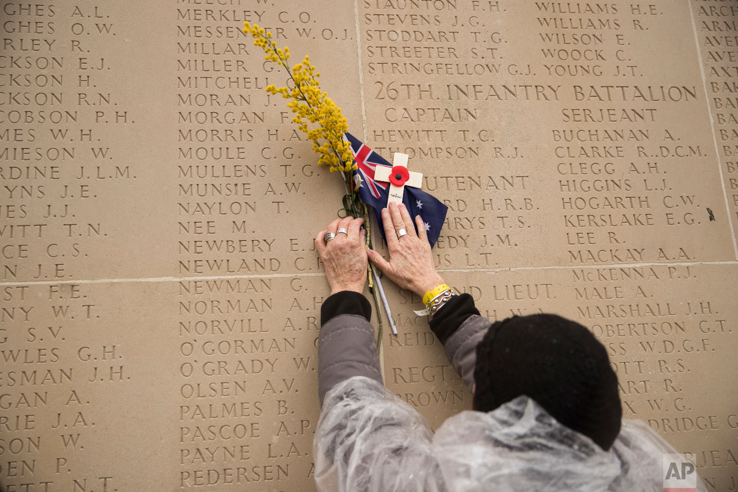 A woman touches a wall with the names of the missing at the WWI Australian National Memorial in Villers-Bretonneux, France, Nov. 11, 2018. (AP Photo/Francisco Seco)