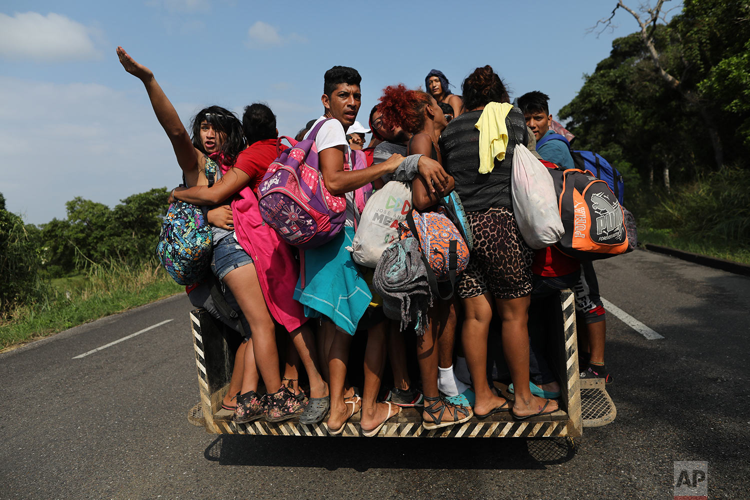 In this Nov. 2, 2018 photo, members of a group of 50 or so LGBTQ migrants traveling with the migrant caravan hoping to reach the U.S. border, hitch a ride on an overloaded utility truck to Sayula, Mexico.  (AP Photo/Rodrigo Abd)