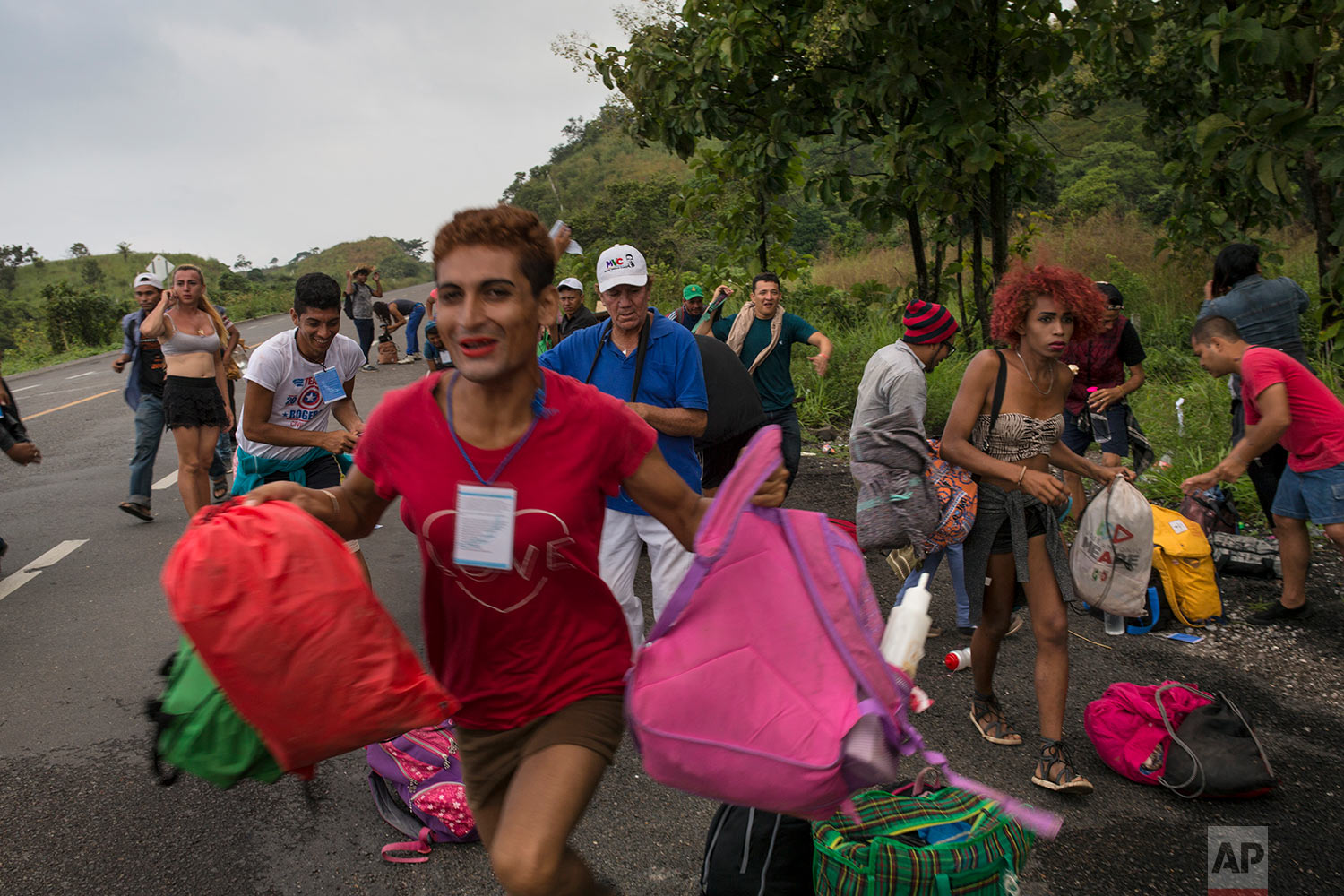 In this Nov. 2, 2018 photo, members of a LGBTQ group who are traveling with the Central American migrants caravan hoping to reach the U.S. border, run towards a truck who stopped to give them a ride, on the road to Sayula, Mexico. (AP Photo/Rodrigo Abd)