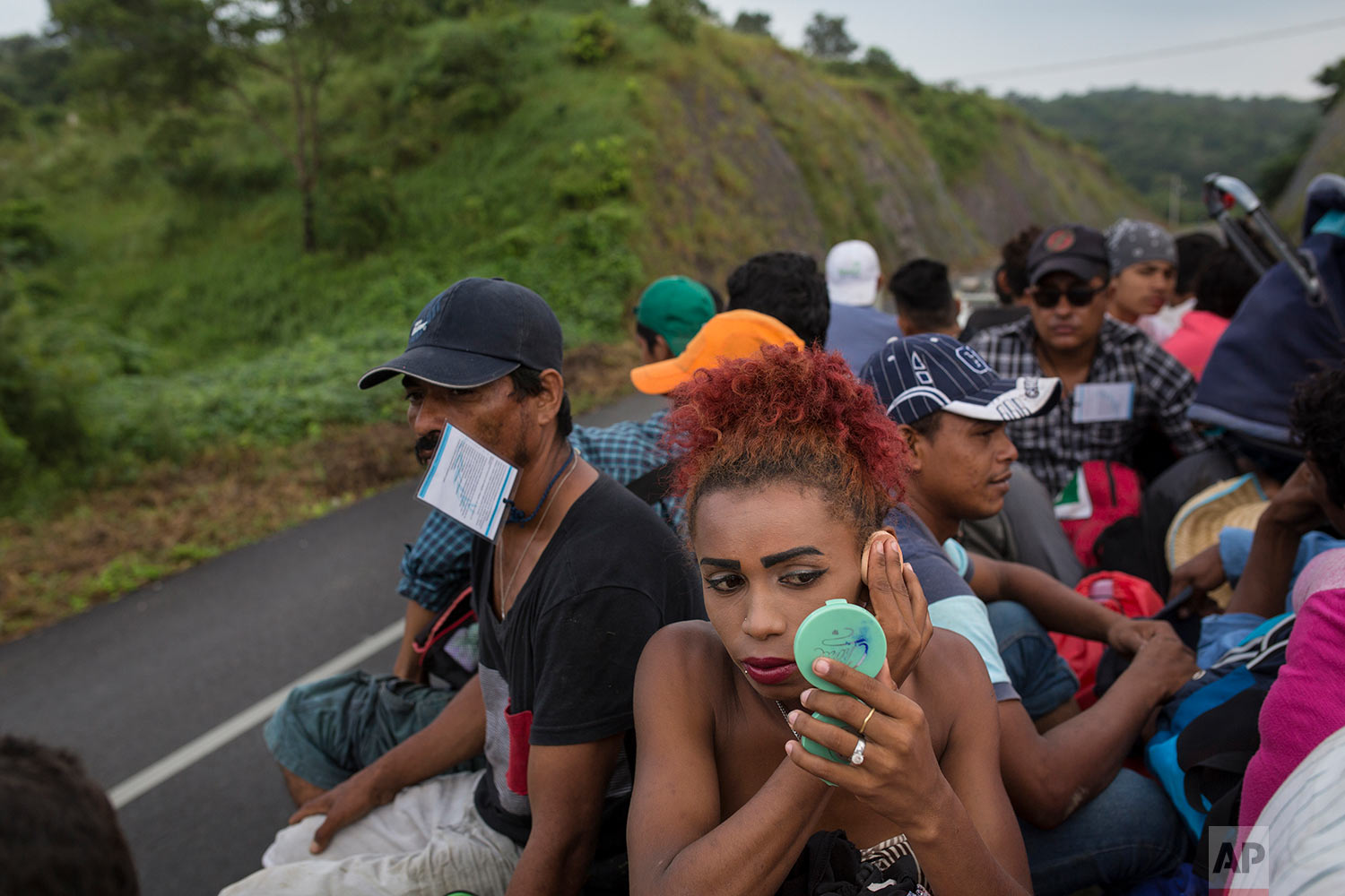 In this Nov. 2, 2018 photo, Honduran transgender Alexa Amaya, who is part of a group of 50 or so LGBTQ migrants traveling with the migrant caravan hoping to reach the U.S. border, uses a compact miror to apply makeup while riding in the back of a flatbed truck to Sayula, Mexico. AP Photo/Rodrigo Abd)