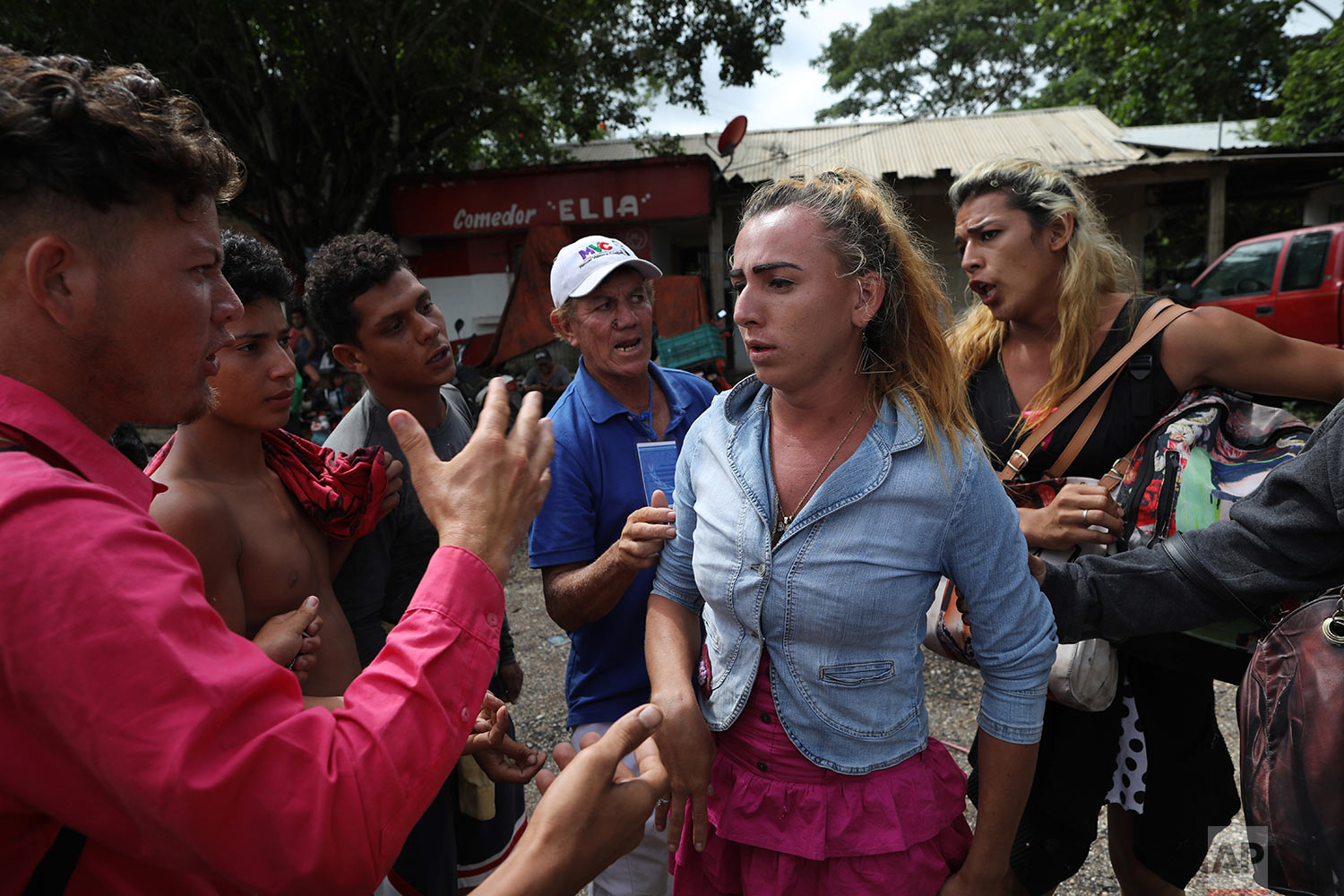 In this Nov. 3, 2018 photo, Honduran transgender Mariela Mejia, 22, who is traveling with the Central American migrants caravan hoping to reach the U.S. border, is pressured into sharing a wad of money given to her by a passerby, on the road to Isla, Mexico. (AP Photo/Rodrigo Abd)