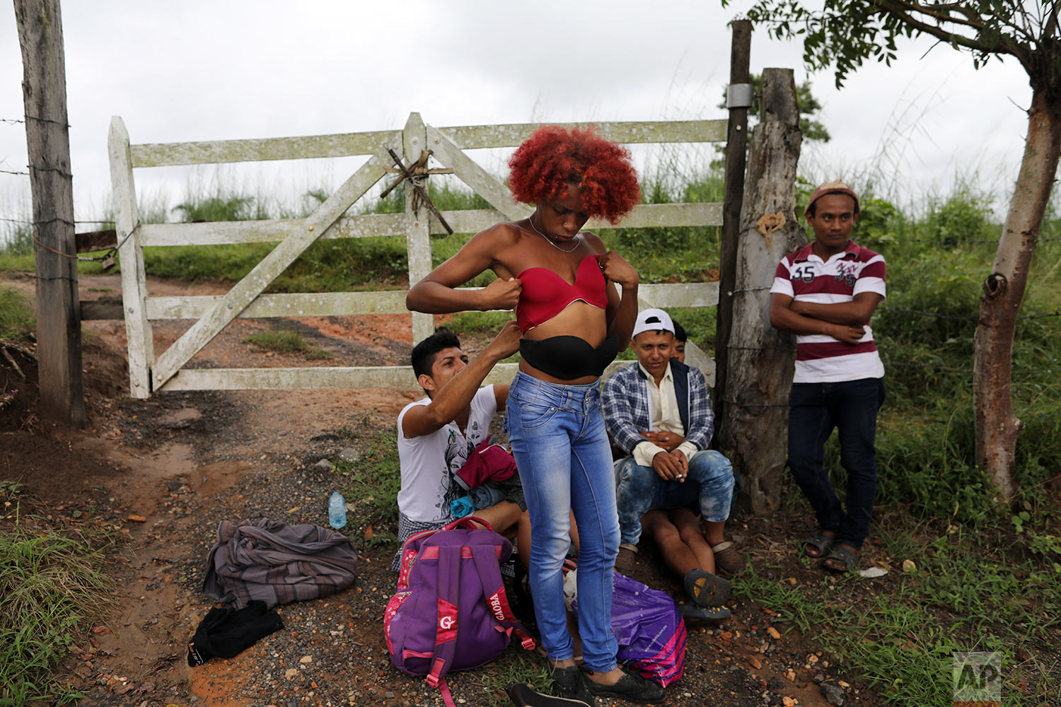In this Nov. 3, 2018 photo, Honduran transgender Alexa Amaya, who is traveling with the migrant caravan hoping to reach the U.S. border, tries on a pushup bra she selected from a pile of donated clothing left alongside the road to Sayula, Mexico. (AP Photo/Rodrigo Abd)