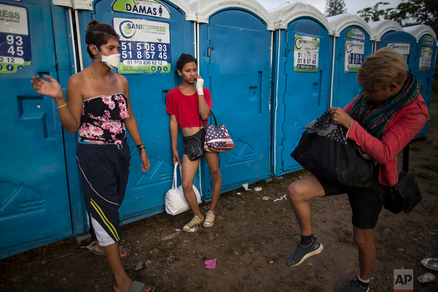In this Nov. 1, 2018 photo, Valentina Guerrero, of El Salvador, right, and Sinai Cortez, from Nicaragua, center, part of about 50 LGBTQ migrants who are traveling with the caravan hoping to reach the U.S. border, wait their turn to use a portable toilet at a temporary shelter in Donaji, Mexico. (AP Photo/Rodrigo Abd)