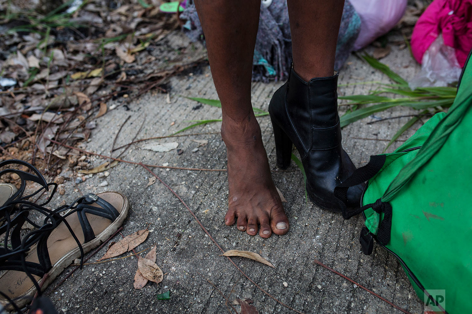 In this Nov. 3, 2018 photo, Honduran transgender Alexa Amaya, who is part of a group of 50 or so LGBTQ migrants traveling with the migrant caravan hoping to reach the U.S. border, tries on donated footwear at a shelter in Sayula, Mexico. (AP Photo/Rodrigo Abd)