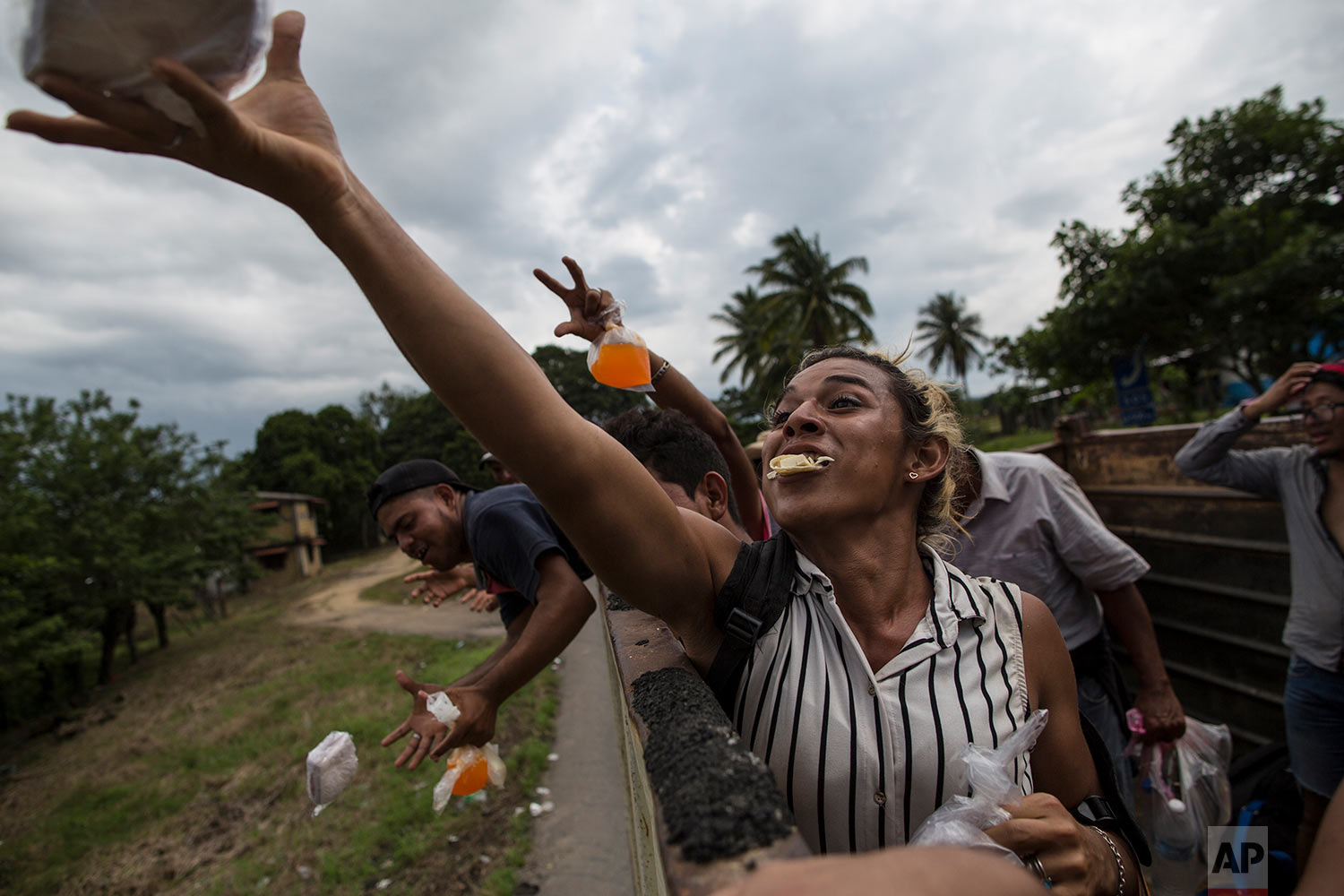 In this Nov. 2, 2018 photo, Honduran transgender Teresa Perez, who is part of a group of 50 or so LGBTQ migrants traveling with the migrant caravan hoping to reach the U.S. border, catches a sandwich tossed by a local, while riding in the back of a truck on the road to Sayula, Mexico. (AP Photo/Rodrigo Abd)